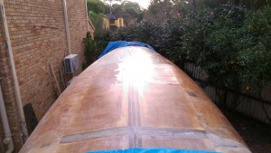 Just over half of the hull of our Didi 40 Cr is now covered in 425 gram double bias glass in West system epoxy resin